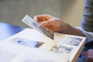 A woman's hand holding up an old photograph above a photo album