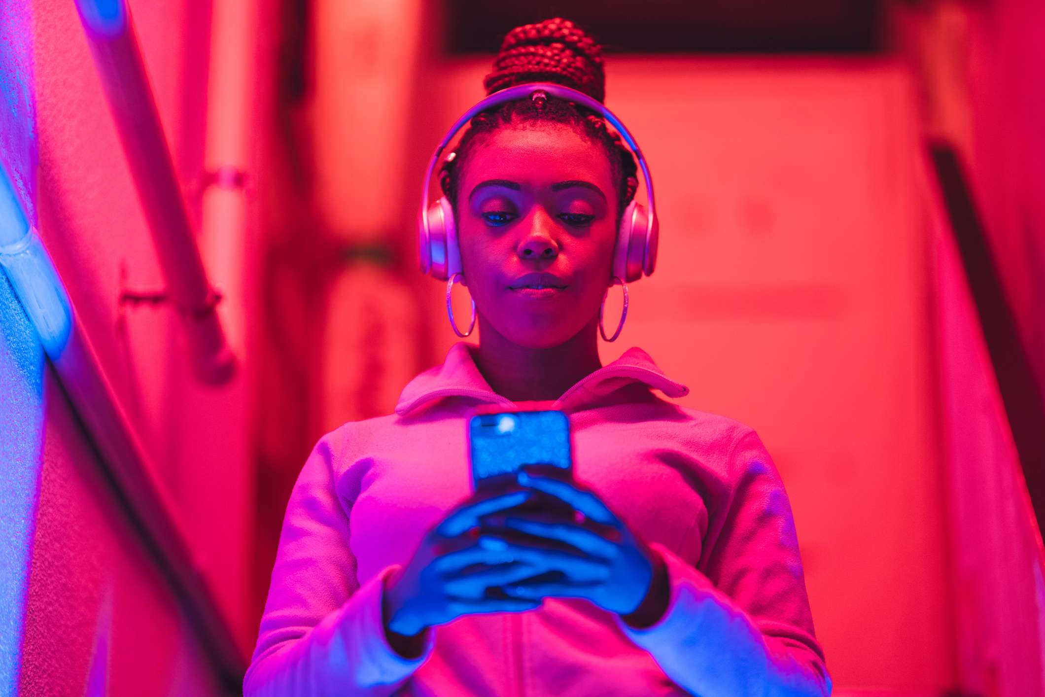 Someone listening to audio from their smartphone through headphones while standing under a neon light.