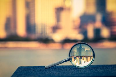 Magnifying glass with image of distant skyline through it
