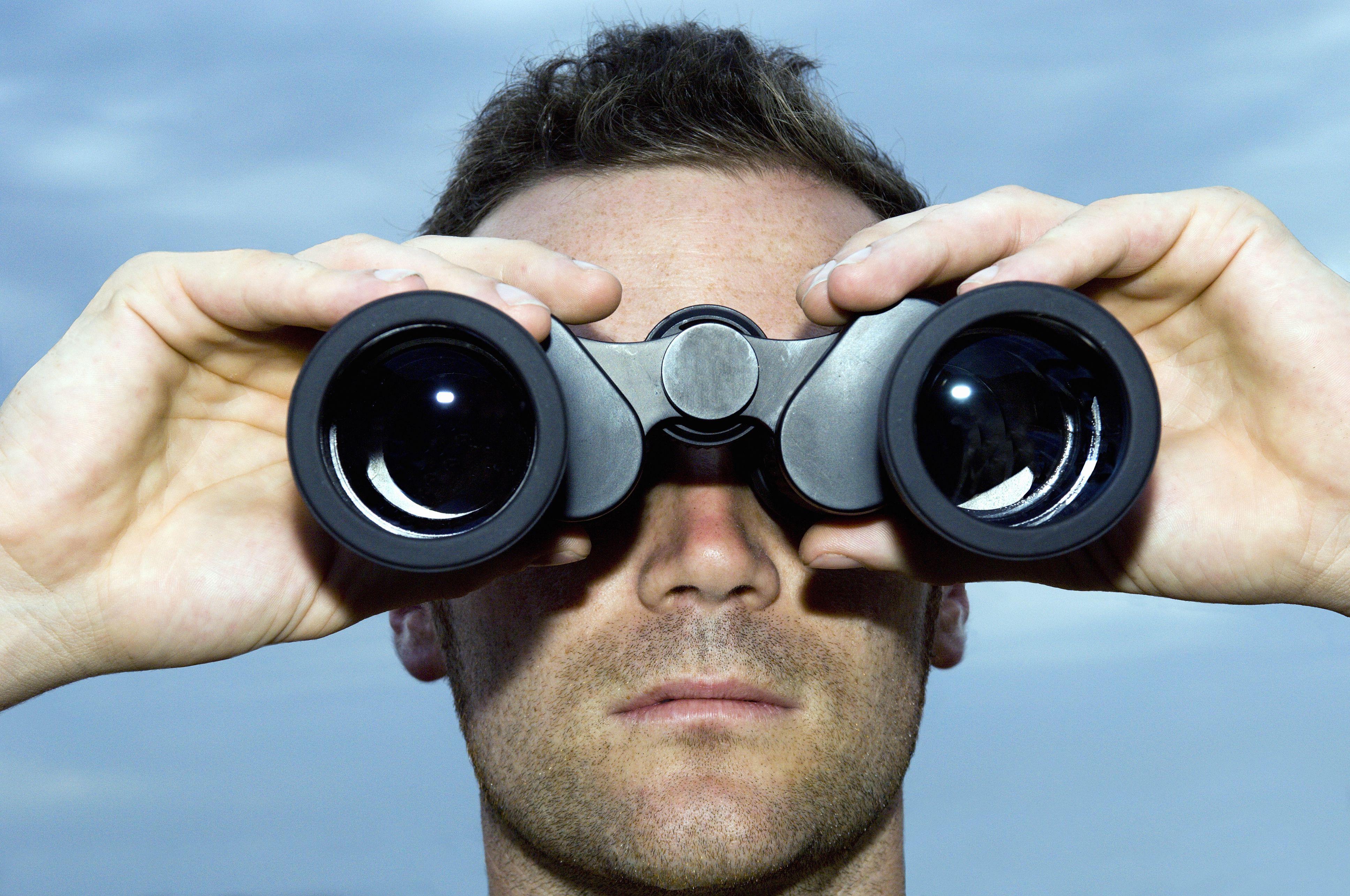 Man looking through binoculars outdoors, close-up