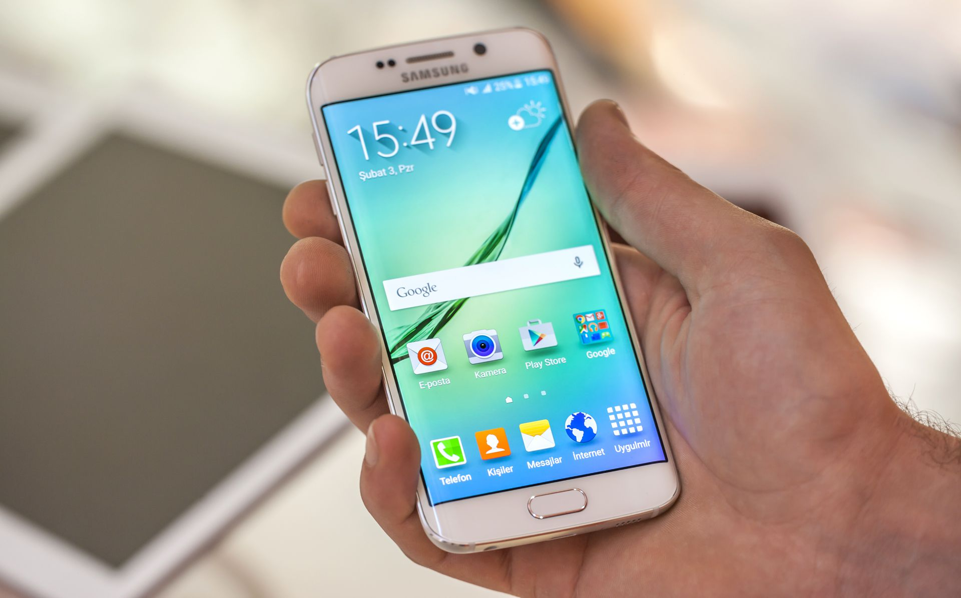 Close-up of a hand holding a Samsung Galaxy S6 Android smartphone.