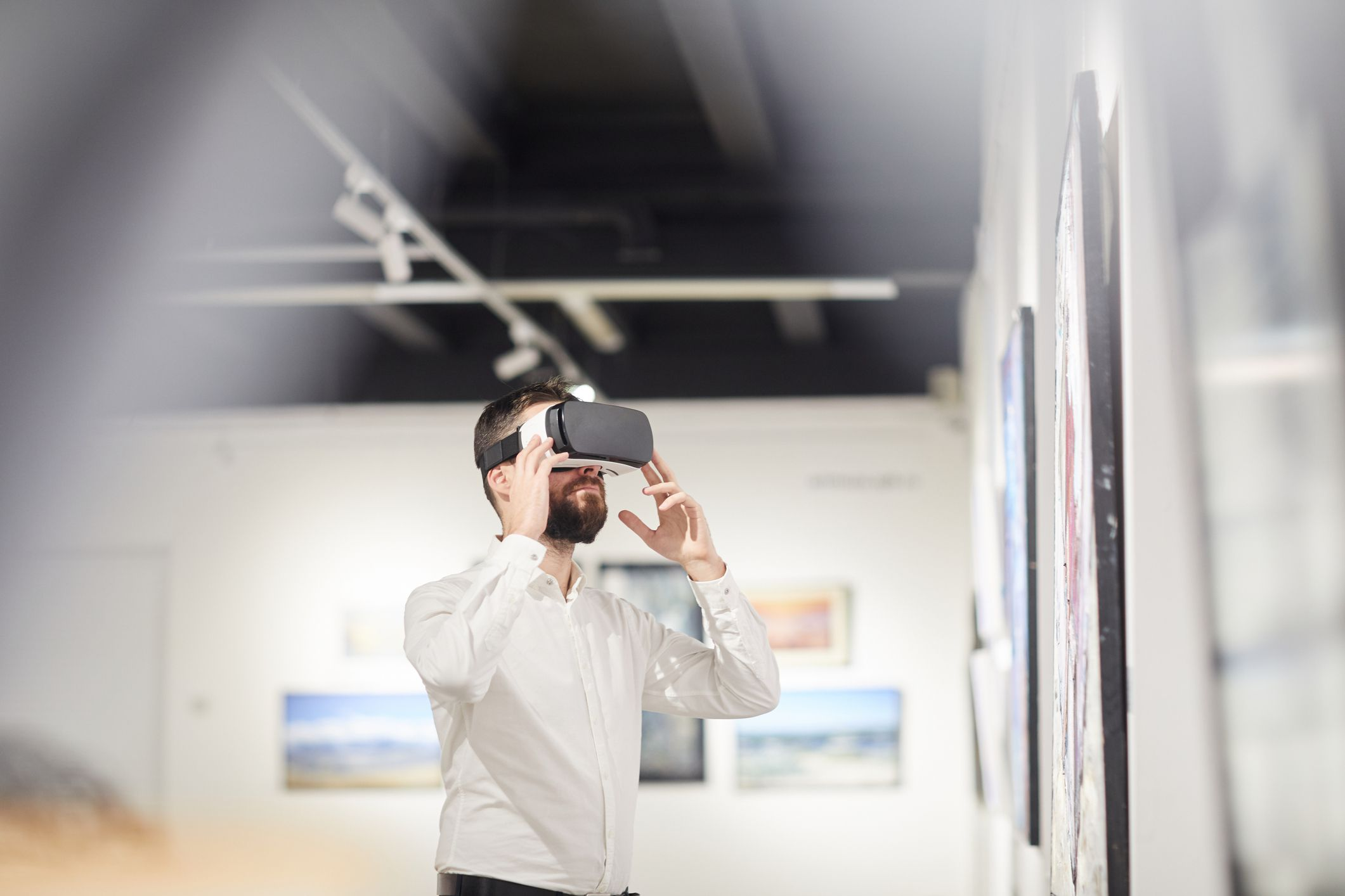 Side view of someone wearing VR Gear while enjoying immersive experience during an exhibition at an art gallery.