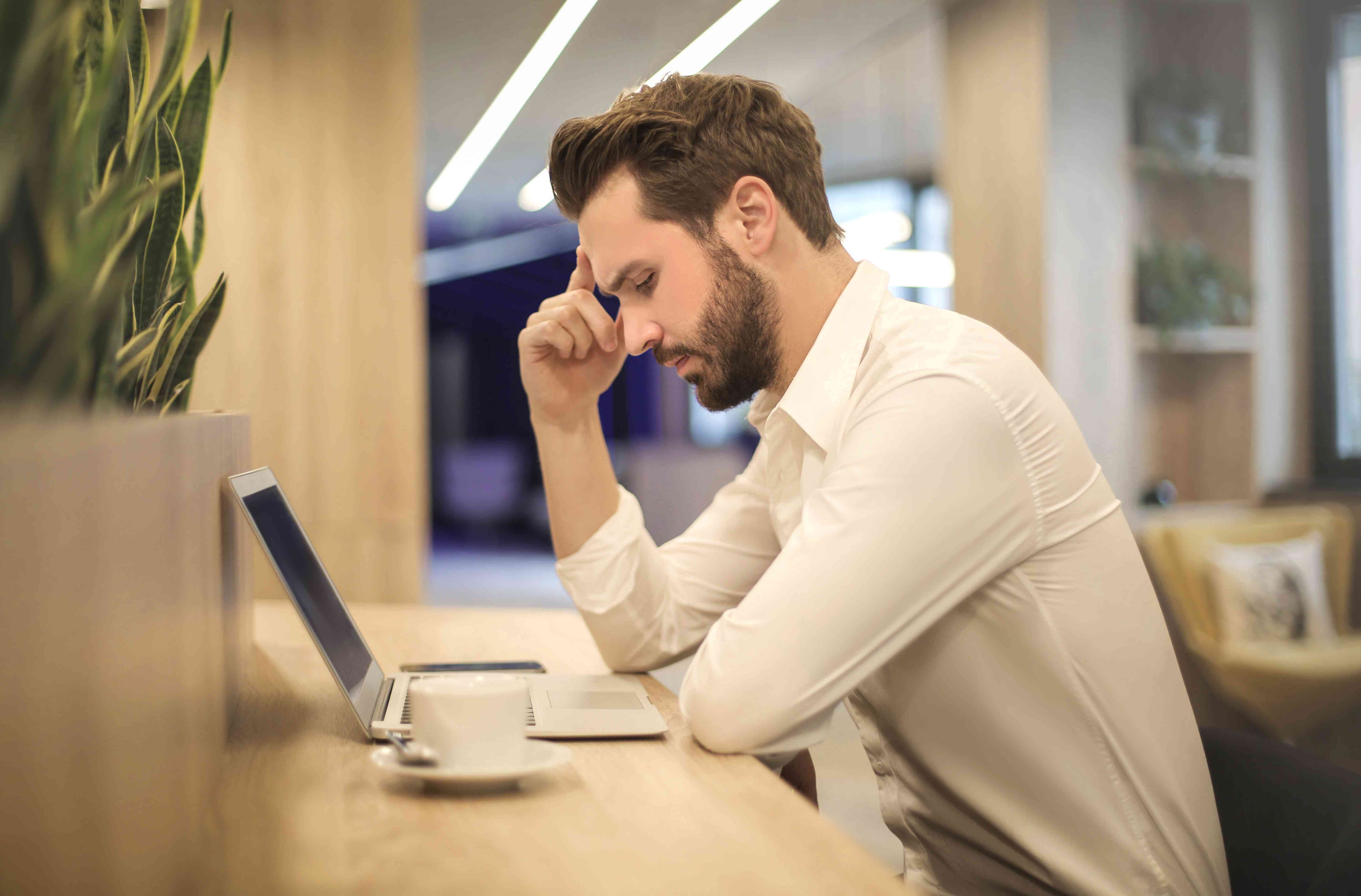 Frustrated businessman with laptop displaying a printer offline error
