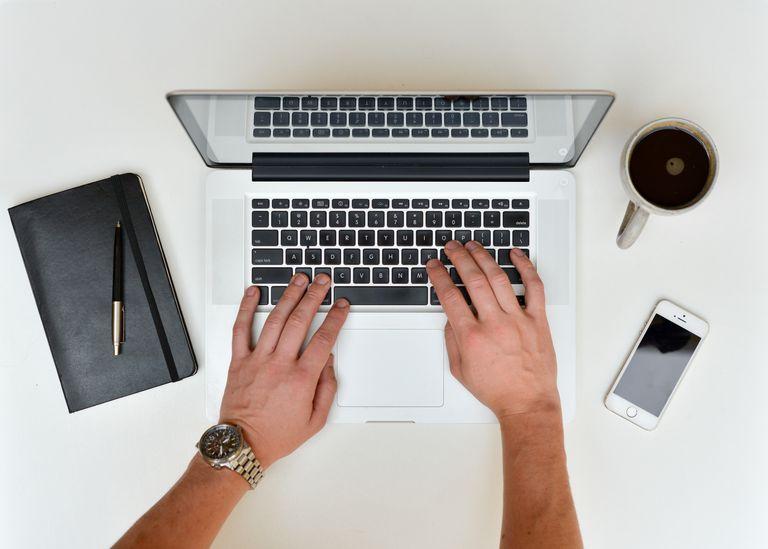 A man using a MacBook on a desk.