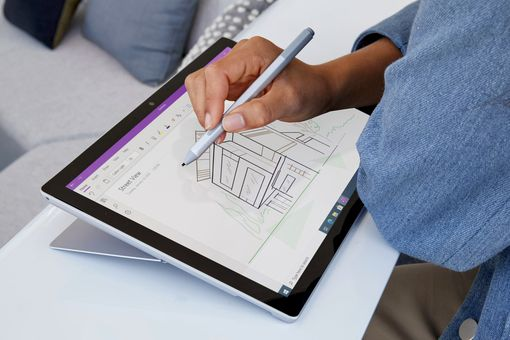 A woman using Microsoft OneNote app on her Surface Pro to draw an image of a house.