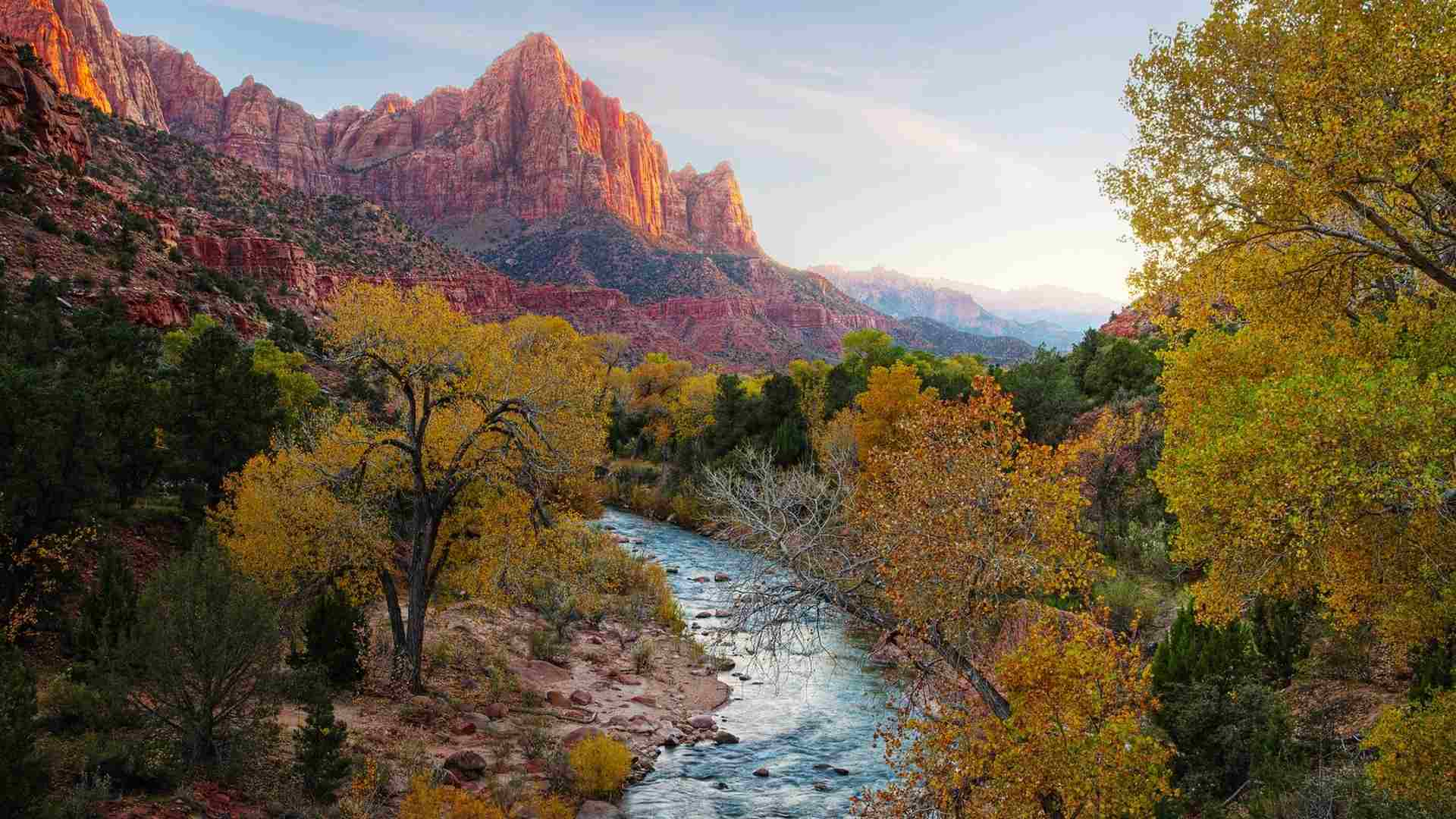 Free autumn wallpaper featuring fall trees by a river with mountains.