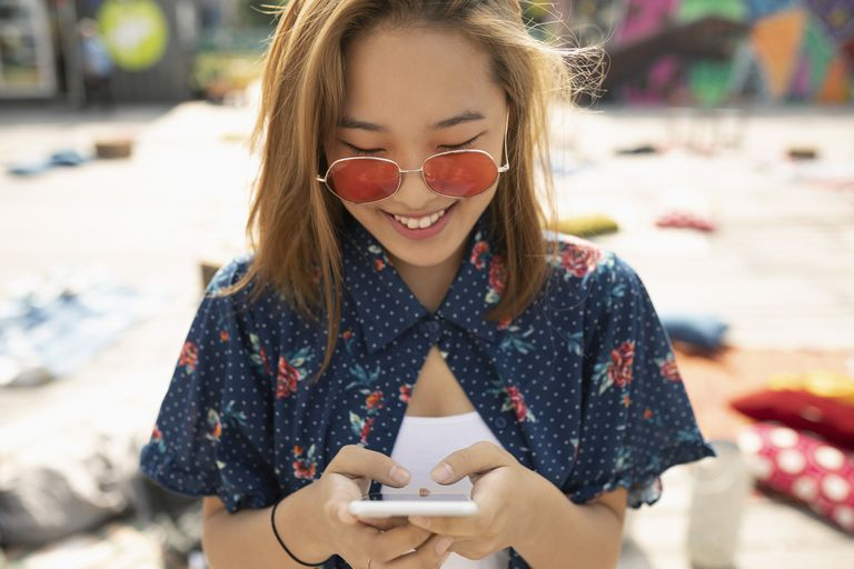 Teenage girl with sunglasses using smart phone texting TC to a friend