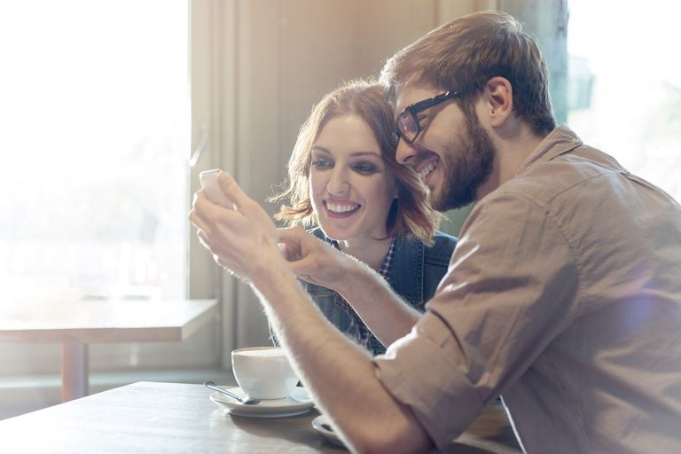 Man and woman looking at phone over coffee