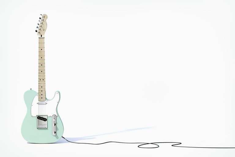 Green electric guitar balancing on white background