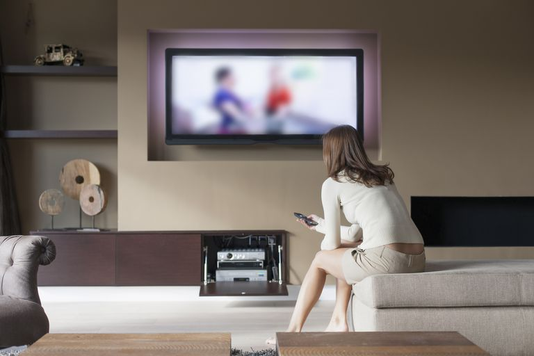 Woman watching television in her living room
