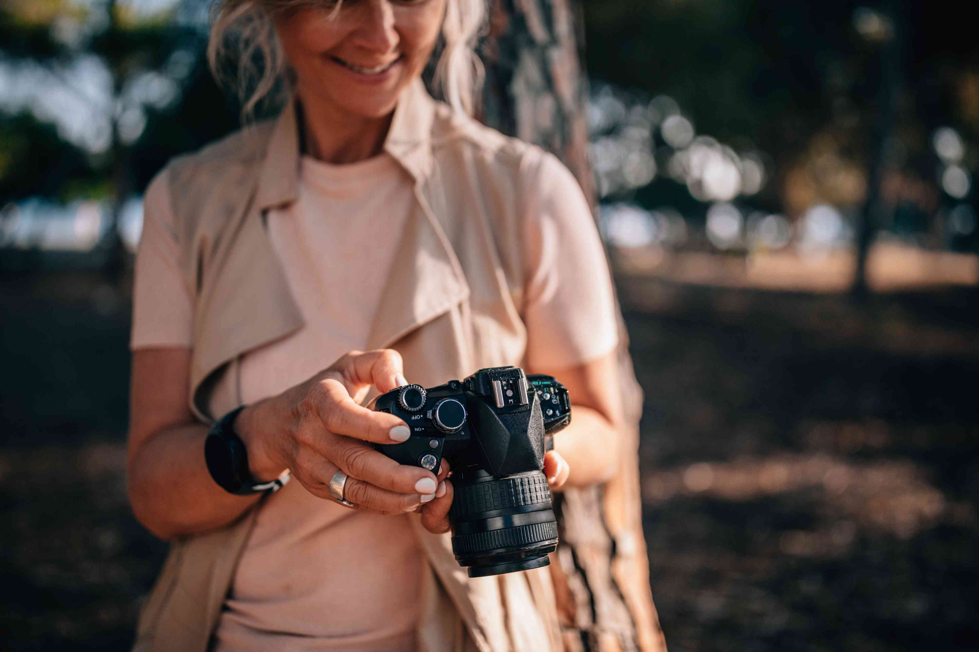 Woman using camera and looking at photos in nature