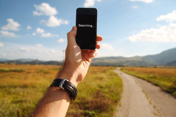 A man holding a smartphone while searching for a cellular network signal.
