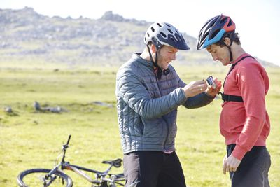 Cyclists on hillside attaching action camera to friend