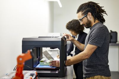 Sideview of someone using a 3D printer.