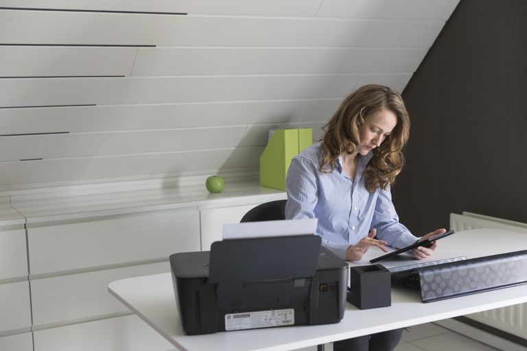 Mid-adult woman working with tablet in office