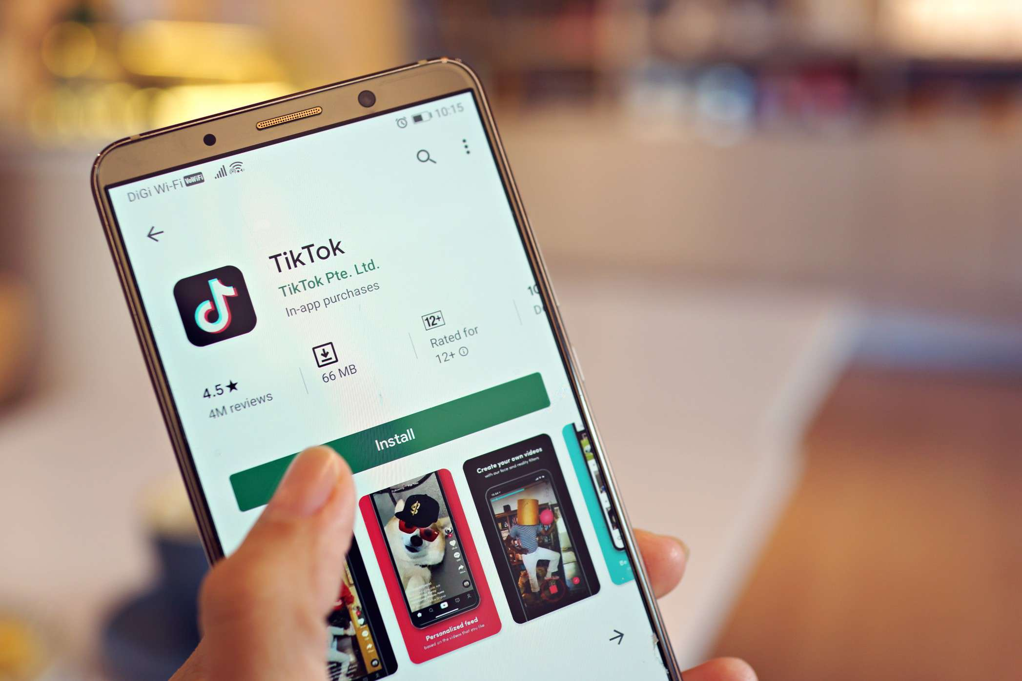 A hand holding a smartphone with the TikTop app show in an App Store.
