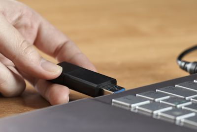 Woman's hand putting PC stick into laptop