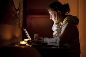 Woman looking at computer in dark room
