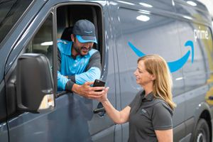 Delivery man in Amazon Prime truck showing phone to a woman
