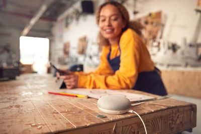 A woman smiling at a woodworking table while looking at a smart speaker in the corner