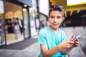 Boy with his mobile phone in a shopping center