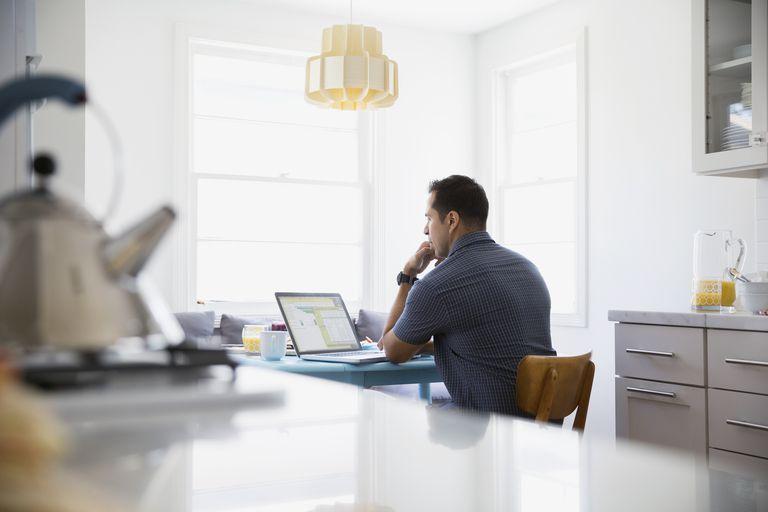man using computer at kitchen table