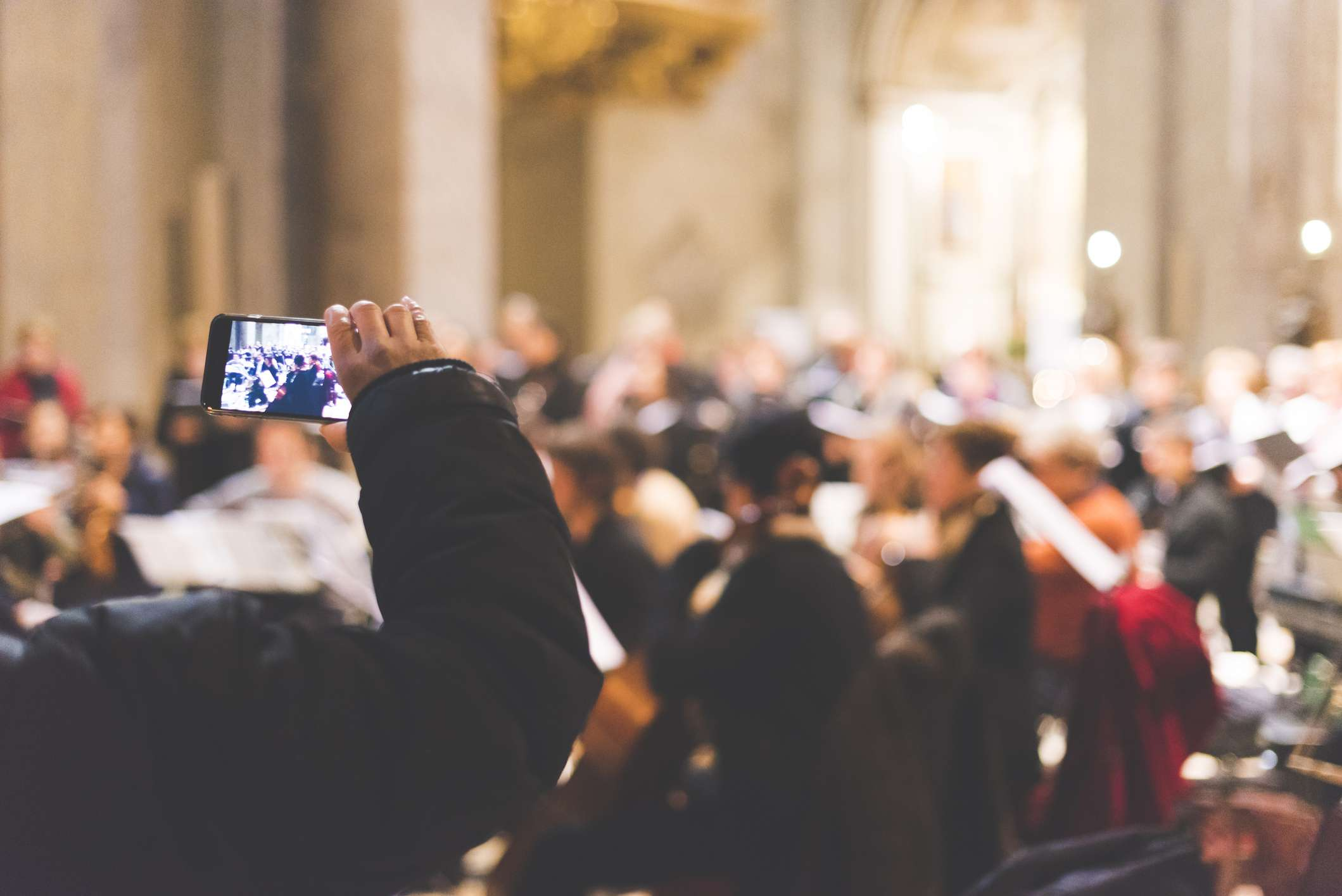 Person recording an orchestra on a smartphone
