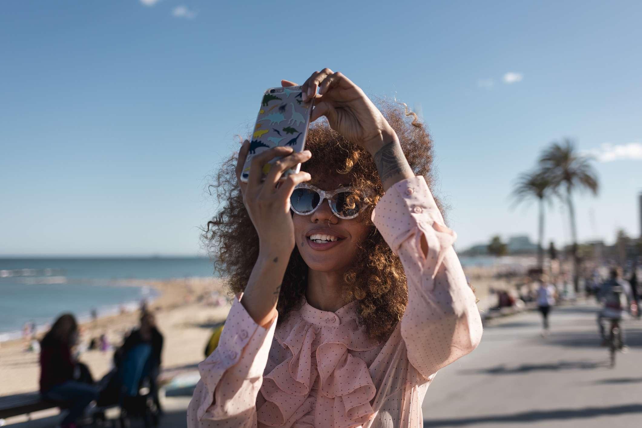 Someone taking selfies at a seaside promenade.