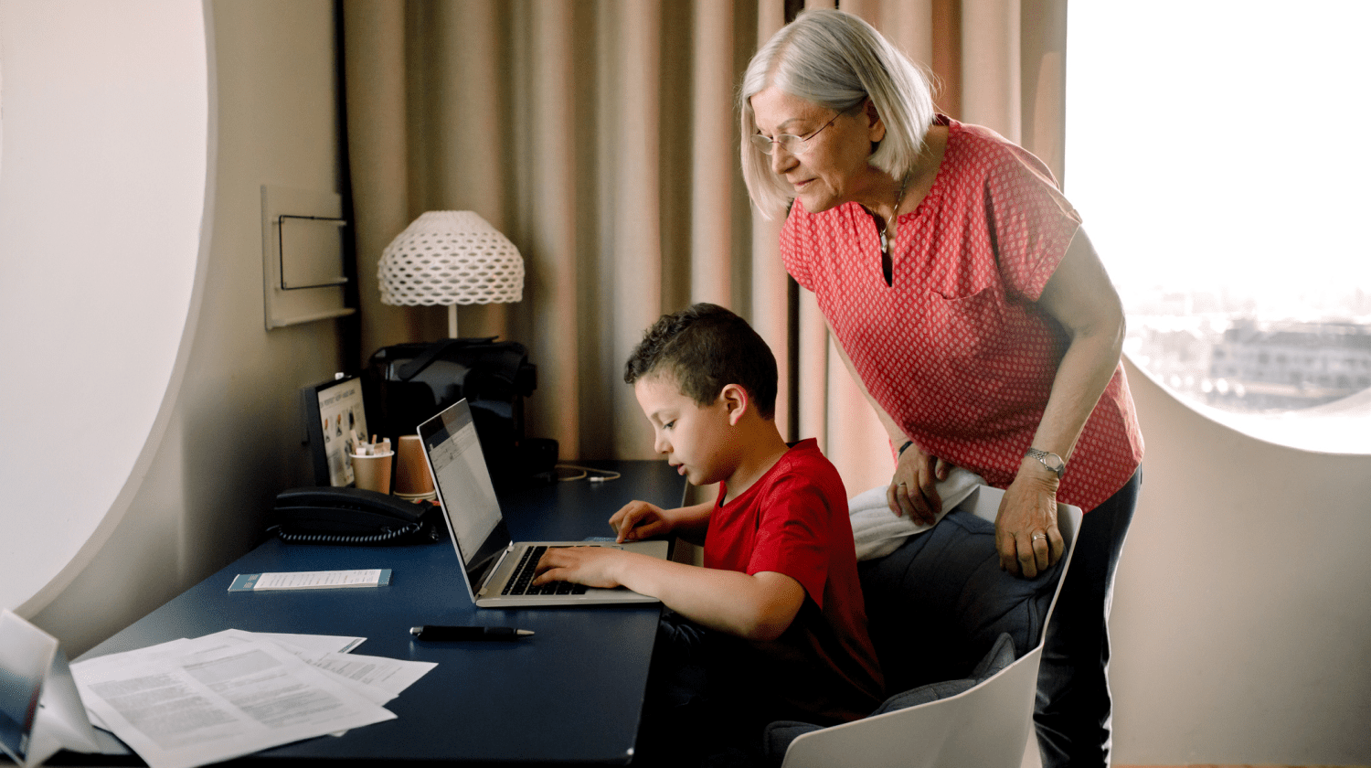 Image of a grandmother using the computer with a kid