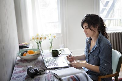 Young Woman Writing by Computer in Apartment.