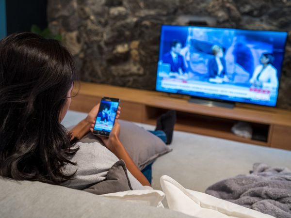 A woman watching a video on her TV and phone at the same time