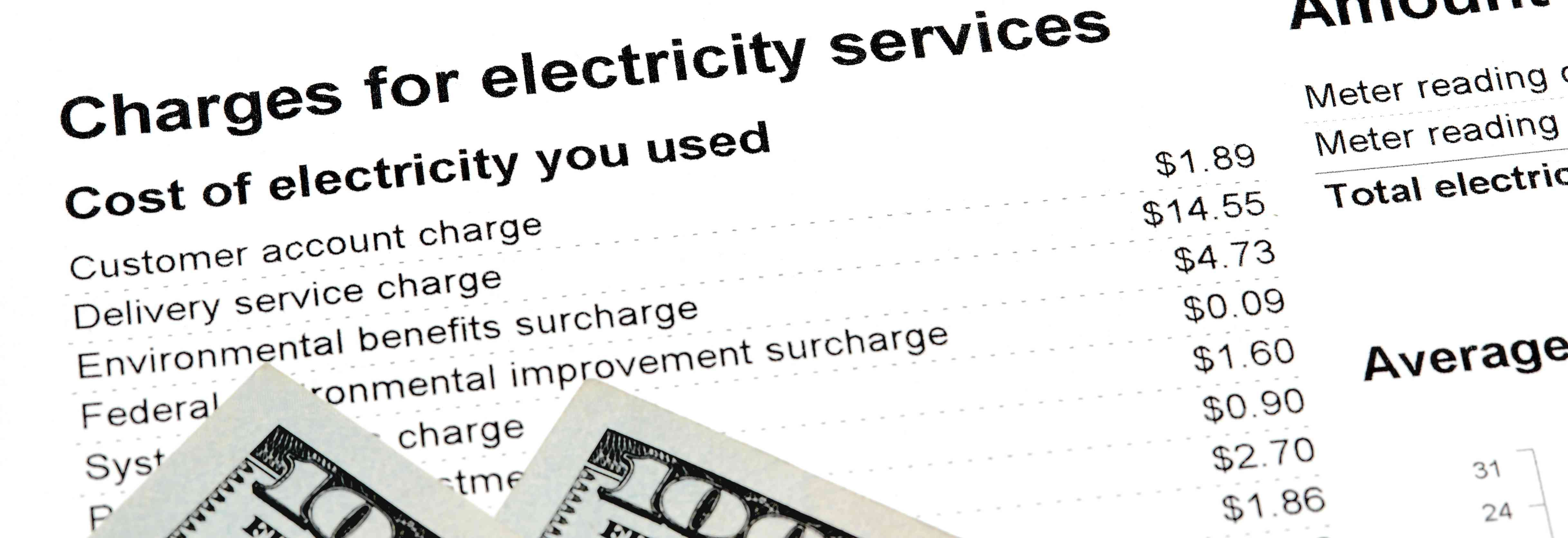 Sample electric bill with $100 bills on top.