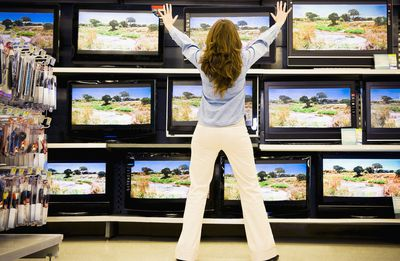 Woman Standing In Electronics Store Facing TVs