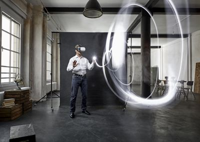 man with vr glasses light painting in front of black backdrop in loft