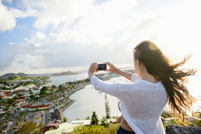 A woman taking a photo with a phone in an exotic locale.