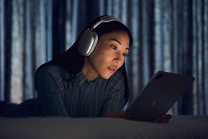 Someone listening to an iPad with AirPods Max.