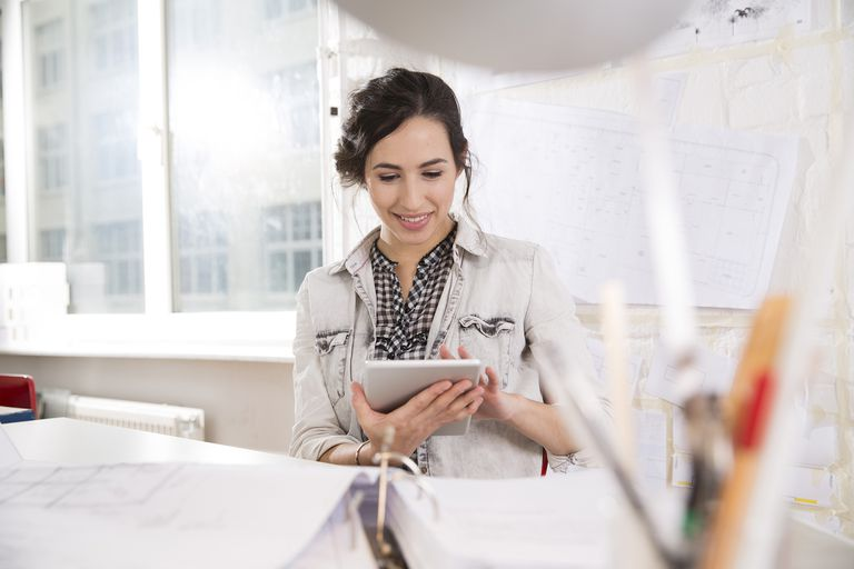 Portrait of Young Female Architect With Digital Tablet at Her Desktop in Office