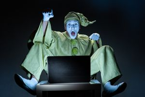 A mime looking at a laptop with surprised look on his face