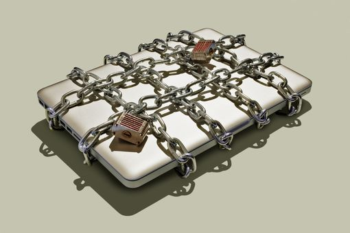 A photo illustration of a computer wrapped in chains.