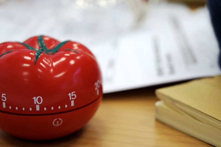 Tomato shaped timer with blurred papers in the background