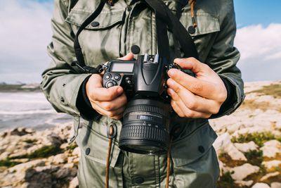 A photographer checks his shots on DSLR camera