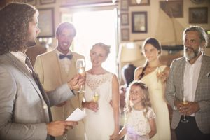 Best man toasting with champagne and giving speech during wedding reception.