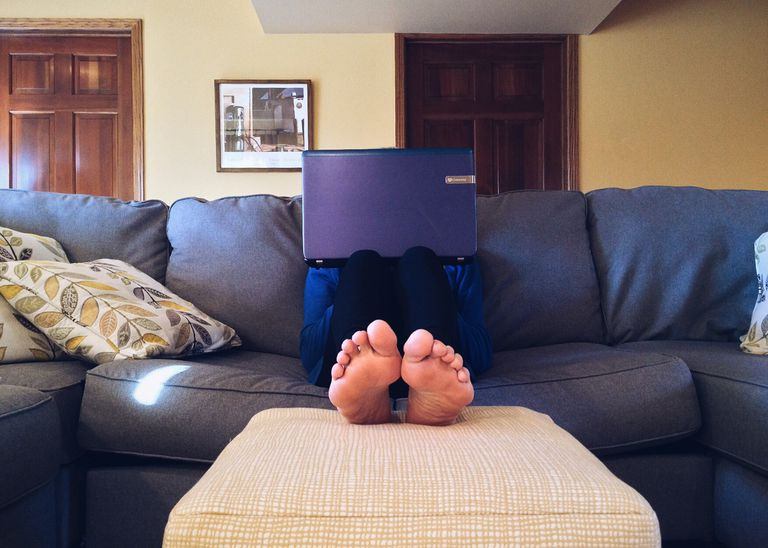 Barefoot person using laptop on couch