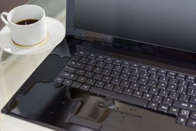 spilled coffee on a laptop with a coffee cup next to the laptop