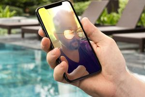 Snapchat user image with filter on mobile phone held in a man's hand