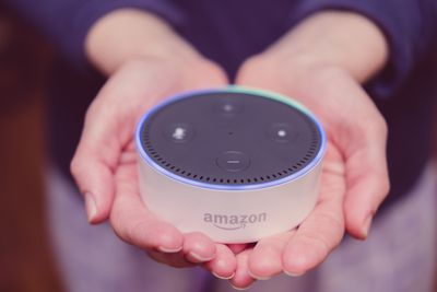 A person holding an Amazon Echo device in two hands.