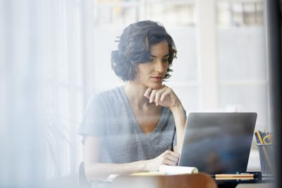 A woman sitting at a desk looking at her laptop