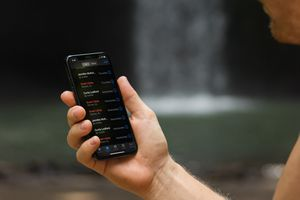 Someone looking at a call log showing 'Scam likely' calls on an iPhone X.
