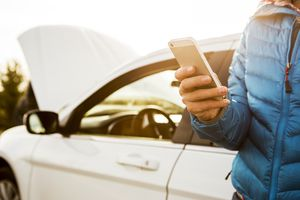 Person using iphone next to car with the hood up
