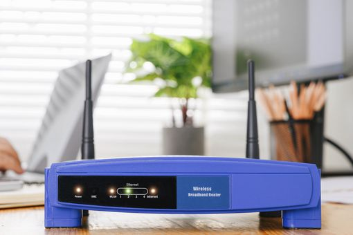 A blue Wi-Fi router sitting on a wooden table with a person accessing the internet on a laptop behind it.